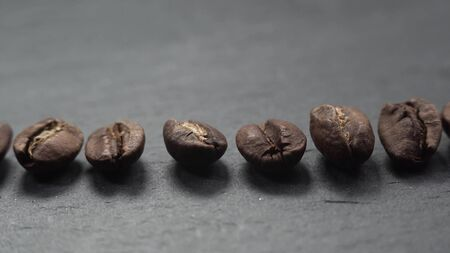 Coffee beans lie in row on stone. The camera slowly fly left over coffee