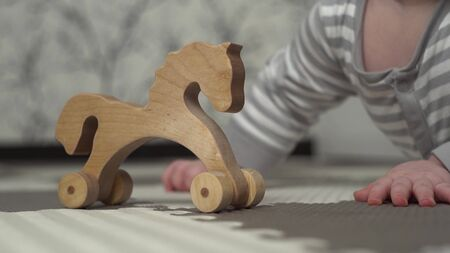 wooden toy horse stands on the floor. In the background, a small child in a gray and white striped pajamas is playing