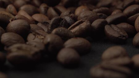 Close up footage of coffee beans falling on black table spinning around. Macro shot of fresh raw coffee
