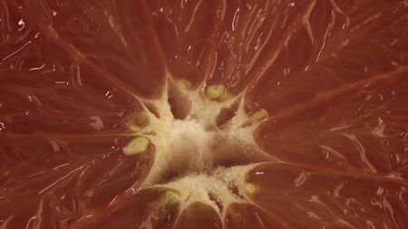 Extreme close up cinematic footage of rotating grapefruit on table. Red fruit spin around its axis Stockfoto