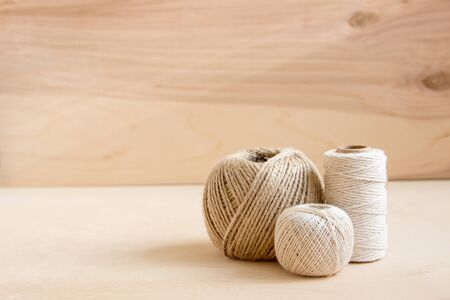 beige threads, twine on wooden background. Natural hemp rope spools on wooden table.