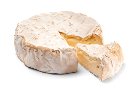 Round Brie cheese with a section cut out over white photo