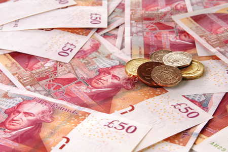 financial item: Background of British Fifty Pound Banknotes and a stack of coins Stock Photo