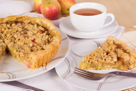 apple crumble: Tea served with rhubarb and apple crumble tart Stock Photo