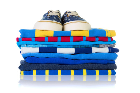 neatly: Stack of colourful summer shirts and a pair of sneakers on top isolated on white background Stock Photo