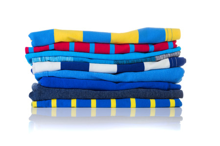 neatly: Neatly folded colourful summer shirts on a white background