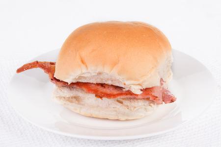 bap: Bacon roll, bap or bun on a white plate. Selective focus Stock Photo