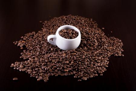 コップ一杯の暗い背景の木のコーヒー豆