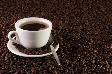 一杯のコーヒーのコーヒー豆の背景に 写真素材