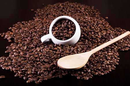 コップ一杯のコーヒー豆と暗い背景に木のスプーンの