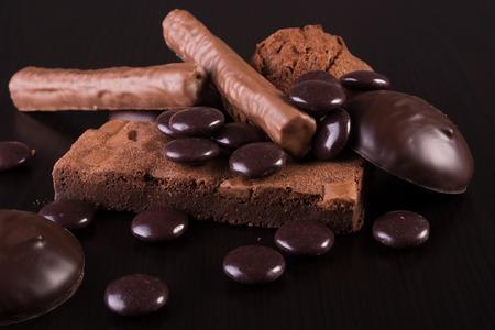 暗い背景の木にチョコレートのお菓子 写真素材