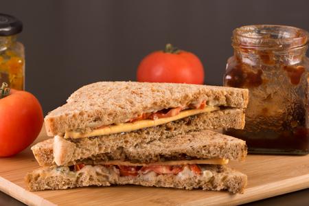 茶色のパンのベジタリアン チーズ、トマト、ピクルスのサンドイッチ。木の板、暗い背景で提供しています
