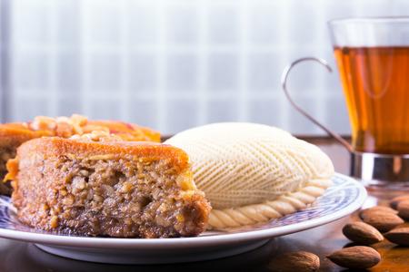 Shekerbura 伝統的な東部甘いペストリーと紅茶とカフェ テーブルや古いコーヒー テーブル上のナッツのバクラヴァ。トーンのイメージ 写真素材