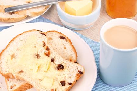 サルタナとミルクティーのカップ フルーツのパンをスライスしました。選択と集中 写真素材