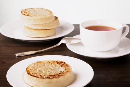 お茶とクランペット暗い木製のテーブル 写真素材