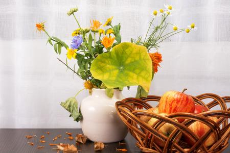 暗い木製の表面に乾燥枝編み細工品のボウルに陶製の花瓶、赤いりんごの花の明るい素朴な花束を残します。