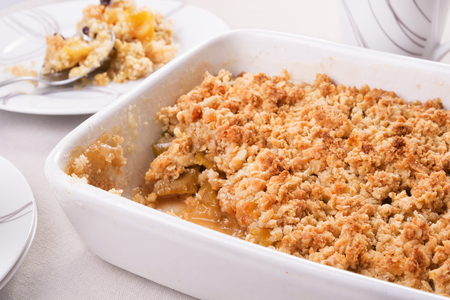Freshly baked apple crumble in a baking dish and a portion on a plate. Selective focus