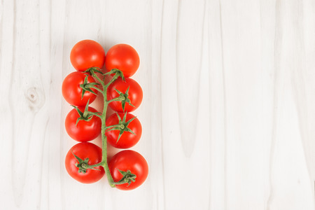 Ripe red tomatoes on the vine on a white wood surface. Top view. Copy space 写真素材