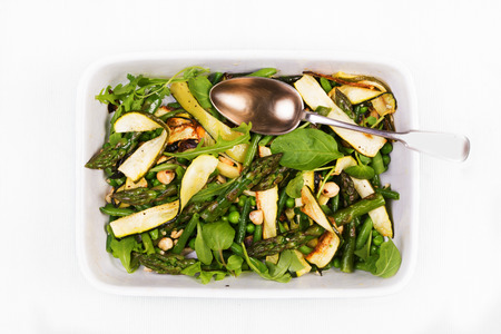 Asparagus, courgette and hazelnut salad in a rectangular dish with a spoon on a white napkin. View from above