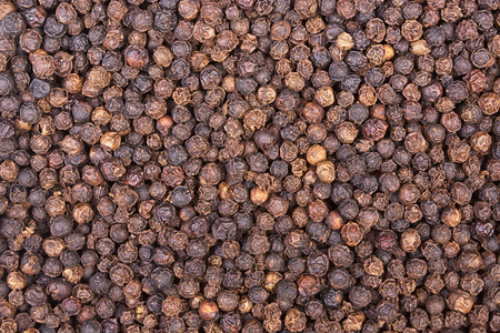 Black pepper corns background. View from above