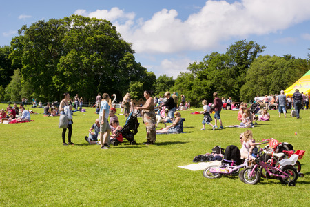 Many people, families with children enjoying a warm sunny day on the lawns of the Calzean estate, Scotland 報道画像