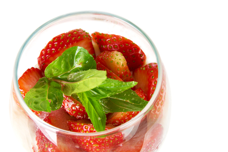Cut strawberries with mint leaves in a glass isolated on a white background 写真素材