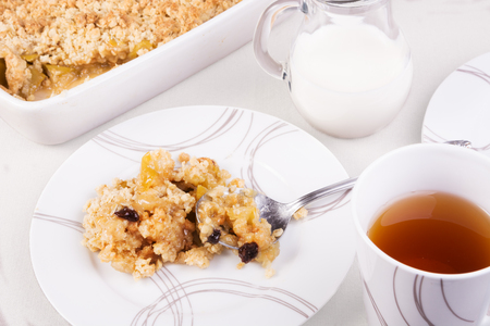 Tea served with traditional British apple or rhubarb crumble. A portion on a plate and crumble in a baking dish 写真素材