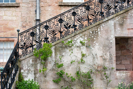 Black forged banister and stone stairs of a porch at Drumlanrig Castle garden, Queensberry Estate, Dumfries and Galloway, Scotland, United Kingdom