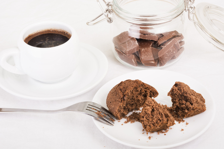 Chocolate muffin broken open on a plate, black coffee and pieces of chocolate in a jar. Selective focus