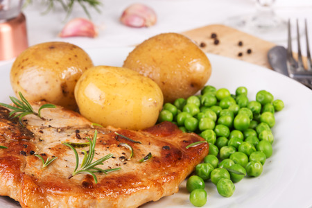 Close up of pork chop, boiled jacket potatoes and green peas served on a plate.Selective focus