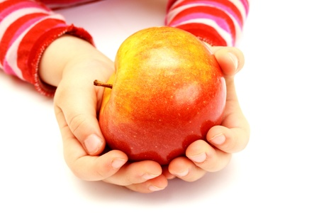 child is holding fresh apple on hands