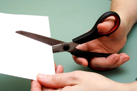 women hand is cutting paper with scissors photo