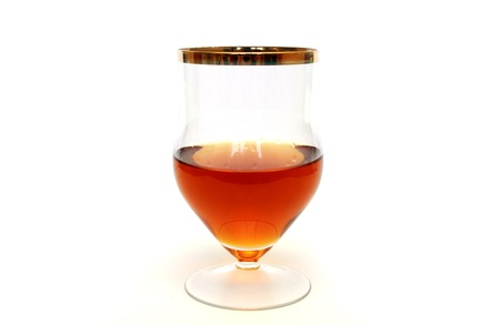 zoomed: Zoomed glass with cognac standing on white background Stock Photo