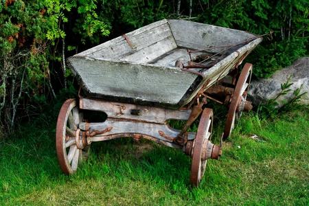 carreta madera: Permanente de vagones viejos y usados cerca de arbustos verdes