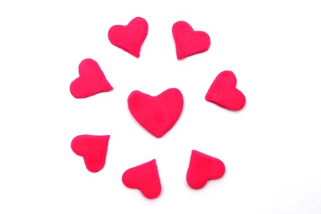 lopsided: Painted to pink hearts of plasticine on background Stock Photo