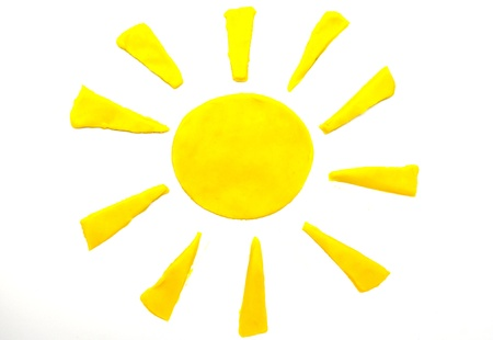 Painted to yellow sun of plasticine on background