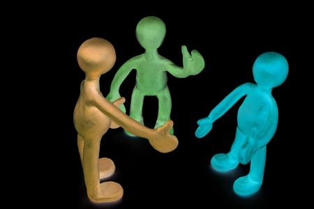 Three shaded plasticine puppets talking on black background photo