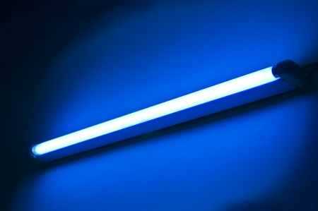 One fluorescent lamp shining on blue colored wall photo