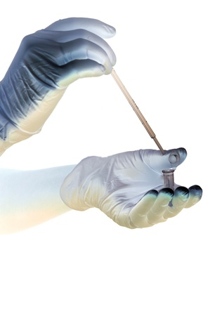 Shaded hands in gloves hold pipette and tube photo
