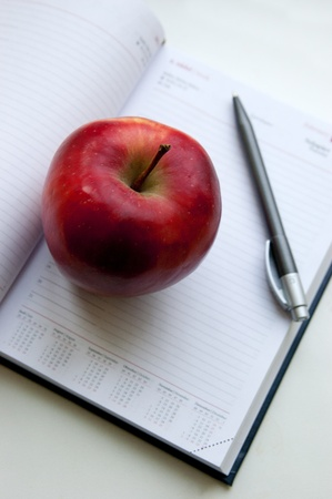 An apple lay on notebook next to pencil photo