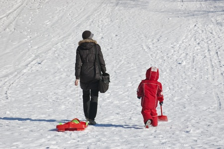 Mother and child going to slide from hill photo