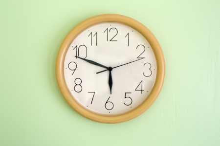 Clock hanging on wall and showing current time Stock Photo - 14304357