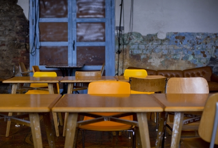 Line of old school desks stationed in room Stock Photo