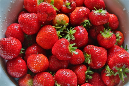 zoomed in: Zoomed fresh strawberries places in round metal bowl