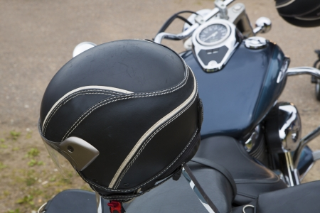 helmet seat: Black round bike helmet on leathered bike seat Stock Photo