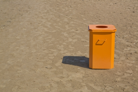 Orange bin  standing in the middle of beach photo
