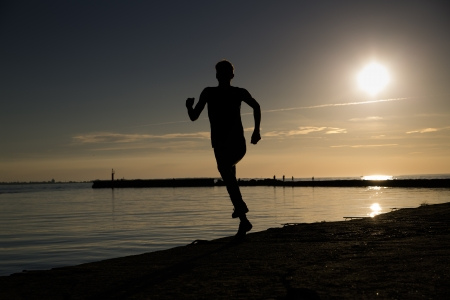 Sportsman making jumpy movement at beach late evening Stock Photo - 14753380