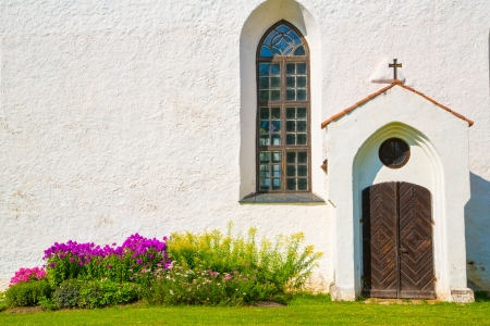 White painted chirch wall with window and door photo