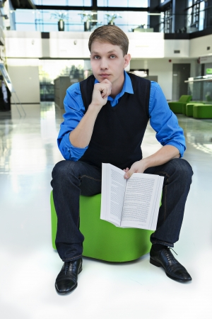 Student sit on green stool with opened book Stock Photo - 15434282