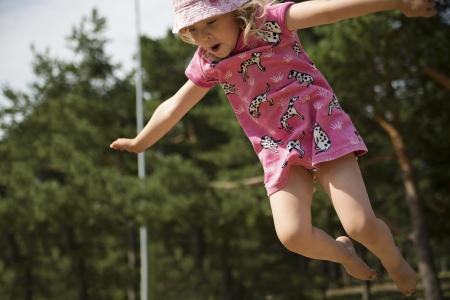 Cute girl is captured on camera while jumping photo